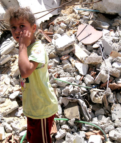 Child in Gaza Beside Destroyed Home
